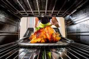 Woman placing turkey in an oven.